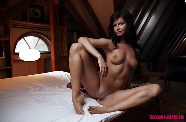 Эрофото: Голое упругое тело брюнетки в полумраке