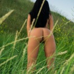 Раздетая брюнетка в траве