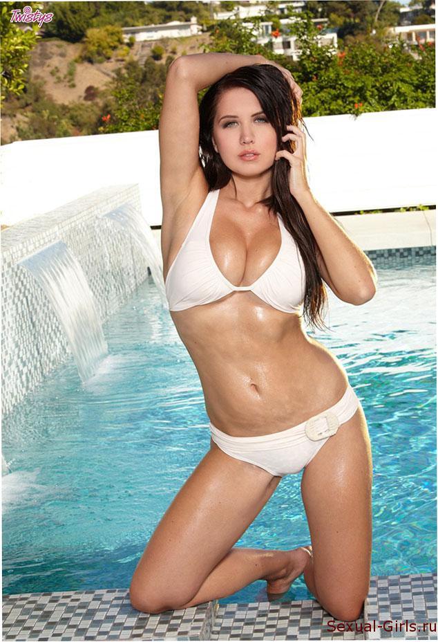 Брюнетка купается голышом в бассейне